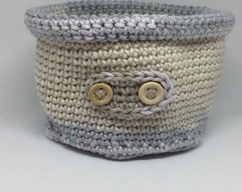 Hand crocheted decorative basket in neutral tones.