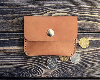 Small leather wallet for bills and coins. Light brown color.