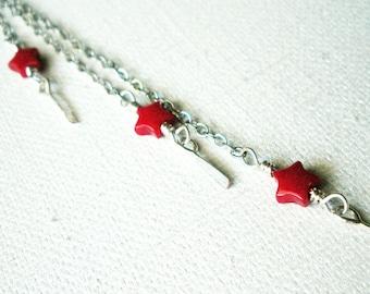 Boucles d'oreilles Duster chaîne à la main avec des étoiles rouges des épaules