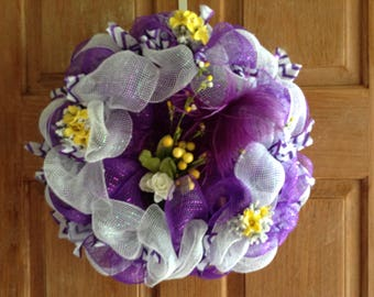 Striking purple and white deco mesh wreath decorated with yellow and white flowers.