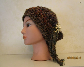 A  ladies crochet tam hat made of homespun and acrylic yarns in earth tone colors, with attached tassel and acrylic pin