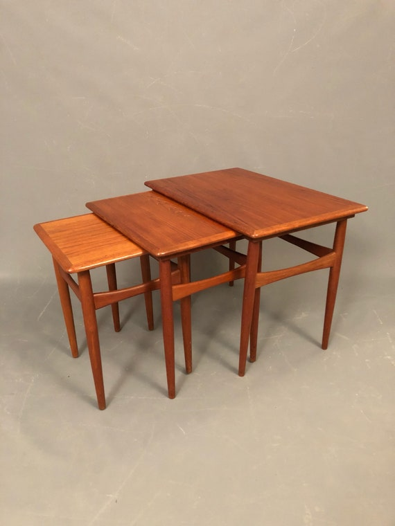 Mid-Century Danish Teak 3 Nesting Tables that slides in with thin legs.