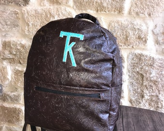 brown tooled leather backpack with livestock brand