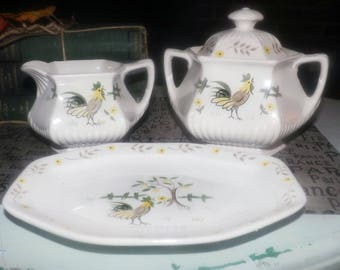 Vintage (1960s) Adams Micratex Real English Ironstone 4-piece set: covered sugar, cream, butter dish. Rooster, yellow flowers, tree.