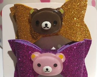 Beautiful foam bows (glittery fuscia with pink bear cabochon and glittery gold with brown bear cabochon) on alligator clips.