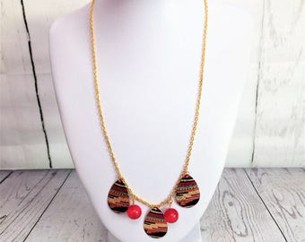 Gold chain  necklace with mulitcoloured teardrop beads and red glass beads.