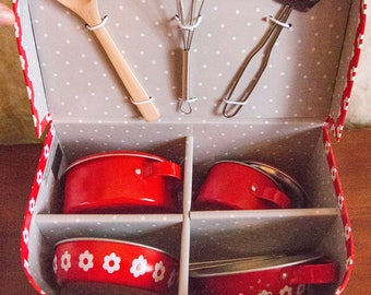 Toy stove with cooking utensils in cardboard suitcase