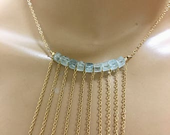 Aqua marine necklace on gold chains cascading square aqua beads.