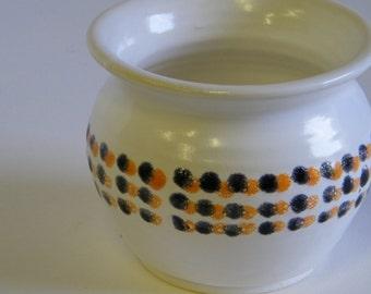 White wheel thrown pot with a Black and Orange dot pattern