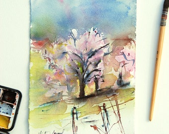 Original watercolor of a cherry blossom in the countryside in France, painting of a tree in pink flowers in spring, farms and meadow