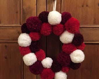 Red and white wool pompom Christmas wreath. Festive, home decor