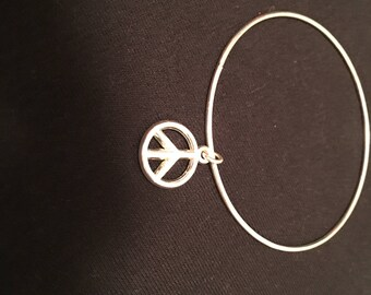 Small silver tone bangle with peace charm.