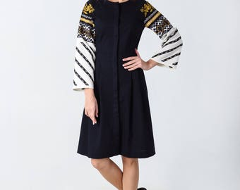 Dark dress with embroidery of geometric pattern on sleeves