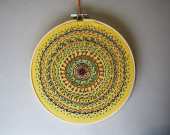 hand embroidered Mandala hoop are on yellow cotton