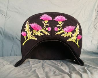 Black cap with pink thistle crown.
