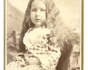 CDV of a little girl with long hair and a lazy eye / carte de visite