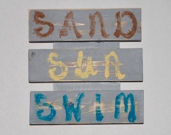 SAND SUN SWIM sign