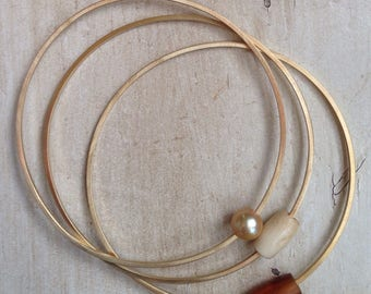 Brass bangles with horn, pearl, and bone beads