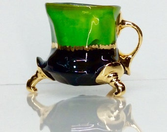 green and black mug with gold and one finger handle