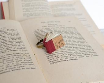 Anello con libro rosso bordeaux e fiori neri disegnati . Anello con libro in miniatura, regalo per scrittori, lettori e librai