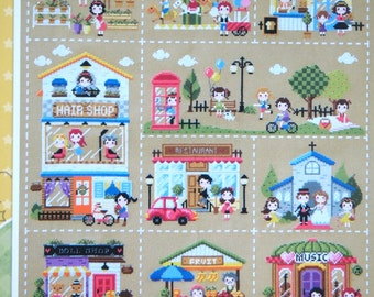 Cute modern cross stitch pattern and kit - mini village featuring  coffee shop, bakery, hair salon, church, restaurant, park, merry go round