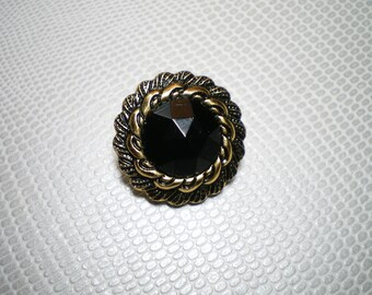 button with black stone wrapped in gold