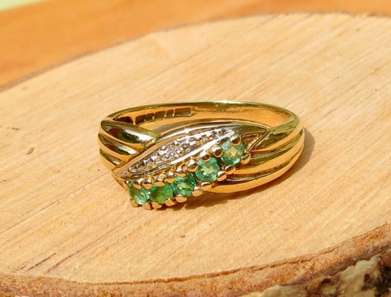 A vintage 9k yellow gold emerald ring with diamond accents.