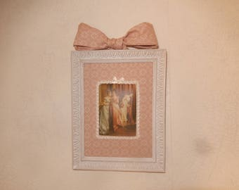 table with old frame with portrait of a romantic woman XVIIIth on fabric and bow