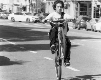 Wheel-up bicyclist black and white photograph