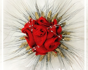 Bouquet made with red jute roses adorned with spike of wheat hat and enriched with pearl threads
