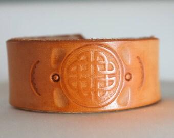 Leather cuff bracelet with Celtic design.