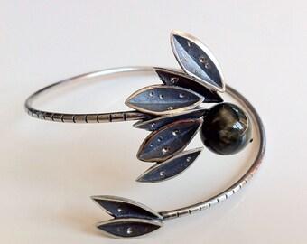 Handmade silver bracelet with leaf motifs and a hawk-eye stone.
