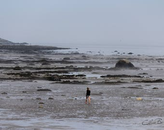 Woman walking by the shore at low tide on a very foggy day
