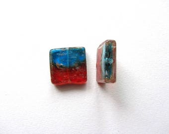 A square glass beads of golden color red and blue