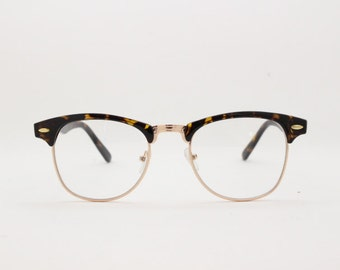 Clubmaster style browline, clear lens, half frame glasses. Tortoise and gold frame spectacles. Prescription horn rimmed eyeglasses.