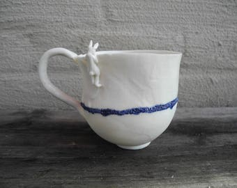 Mug in white porcelain with rabbit looking over the rim - handmade ceramic whimsical mug