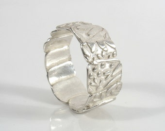Uneven Sterling silver leaves print, put together to create a band.