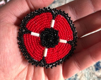 Haudenosaunee made beaded poppy brooch for Remembrance Day/ Veterans featuring white wampum.