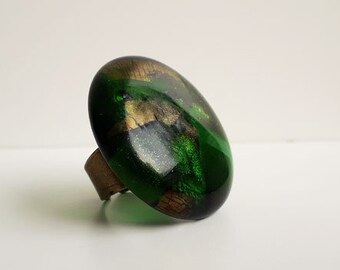 Green glass ring, cast glass in a mix of greens with dichroic and iridescent elements.