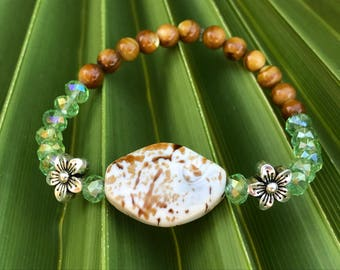 6mm Amber shell and clear light green crystal beads stretch bracelet.