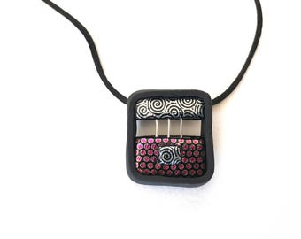 Polymer clay and fused glass pendant with dichroic glass. Pink to orange dots, black and silver swirls