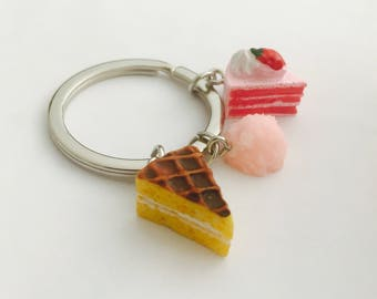 Food keychain, strawberry cake, vanilla cake with chocolate on top, and pink cotton candy ball, dessert