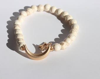 Cream colored beaded bracelet with gold moon and star charm