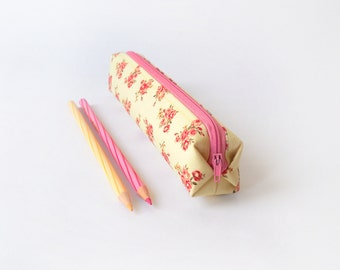 Small pencil case/zipper pouch with roses in shades of pink and red on a pale yellow background, with a bright pink zip