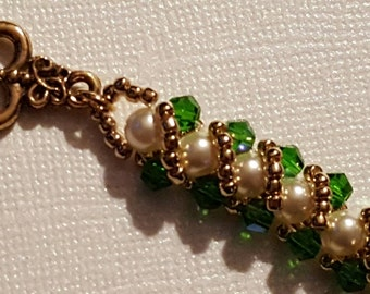 Bracelet of 5mm cream Swarovski Crystal pearls with green AB bicones on either side and wrapped by gold seed beads. Gold heart toggle clasp.