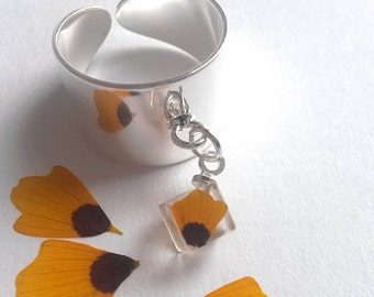 Handmade ring with dried yellow petal of Tagetes patula flower
