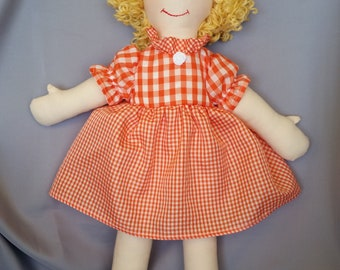 15 inch cloth (rag) doll, with hair and eye color of your choice, comes dressed in an orange gingham dress and white panties