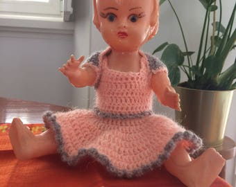 Vintage 1950s doll made of plastic with handmade clothing