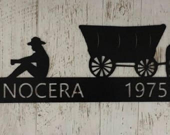 Rustic metal sign with cowboy and covered wagon