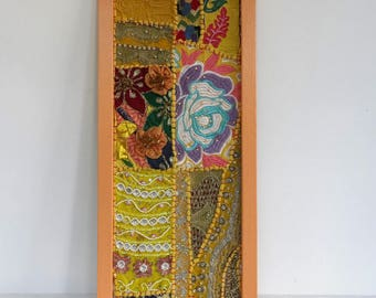 Wall tapestry in yellow, blue and multicolor embroidered patchwork in a painted wooden frame